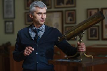 The man posing near the telescope