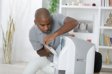 Man working on residential air conditioner