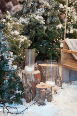 Beautiful Christmas interior design. Close-up of decorated snow-covered Christmas tree with stumps, candles in glasses. Concept of Merry Christmas, winter and New Year