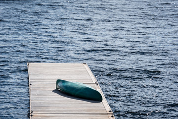 Blue/teal canoe on dock, surrounded by blue water on sunny day