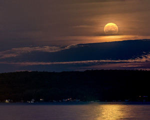 large harvest moon shining through clouds with lake in foreground