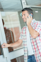 Man on cellphone about to go through glass doors