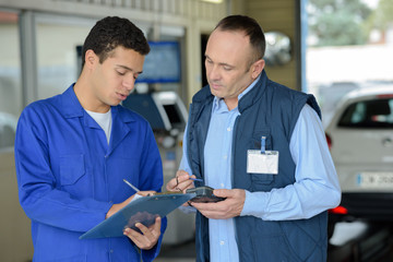 mechanic with clipboard talking to man