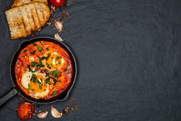 Breakfast. Shakshuka with bread in pan on a black rustic background. Fried eggs with tomatoes. Top view. Space for text. Middle eastern style breakfast or lunch