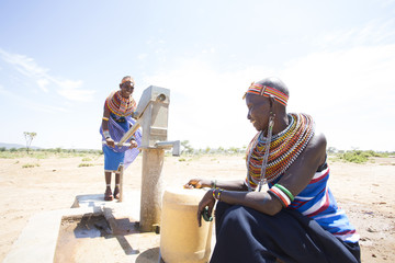 Samburu women collecting water from well in desert.  Kenya.