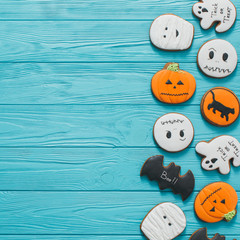 Fresh halloween gingerbread cookies on blue wooden table.