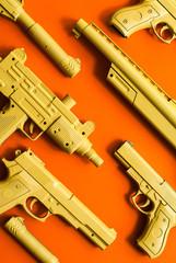 Firearm weapon arsenal replicas on orange background.