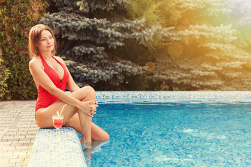Charming woman in red swimming suit in the pool in sunlight