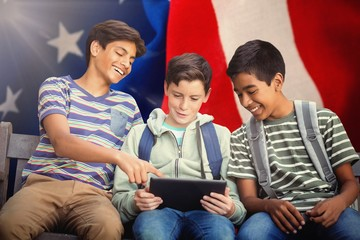 Composite image of boy with friends using digital tablet on