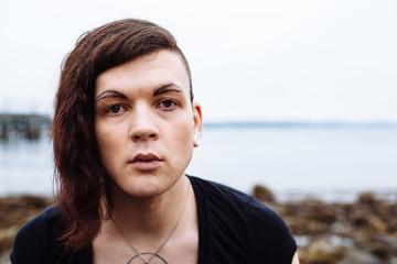 Portrait of gender fluid, transgender person on beach