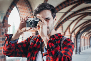 Young man taking picture with retro analog camera