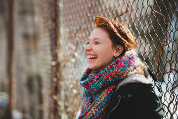 Redhead laughing, standing by fence