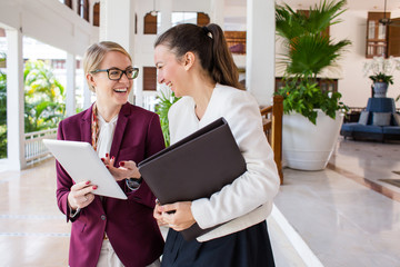 Two young businesswomen laughing