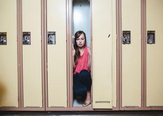 Scared high school student hiding inside locker