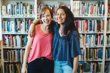 Two high school teensage friends laughing together in library