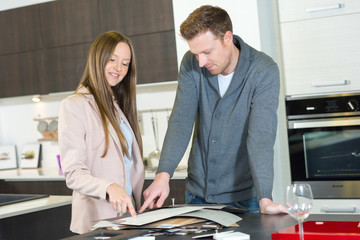 young couple choosing kitchen oven in store and smiling