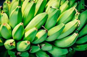 Green Bananas in an Asian Market Stall