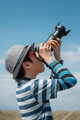 Young boy practicing photography on a sunny day.