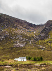 An isolated cottage sits amongst the mountains of Scotland