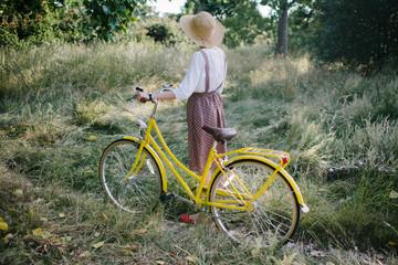 Girl walking her bicycle along