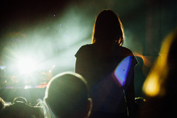 Woman standing in the crowd and watching the show