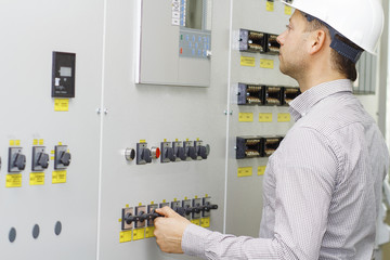 Engineer of tech equipment controls. Worker in white helmet on control panel. Monitoring of technology process.