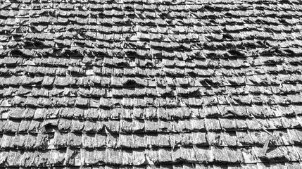 background texture close up of weathered wooden roof shingles in black and white