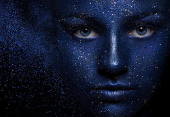 space. beautiful girl face vakrasana blue paint with glitter. The effect of the collapse. the flying particles of powder