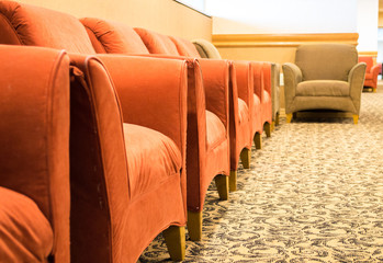 a row of empty cushioned armchairs in a building lobby