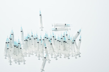 A pile of hypodermic needles spread out on a white surface.