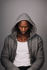 Calm young man in a hoodie looking down