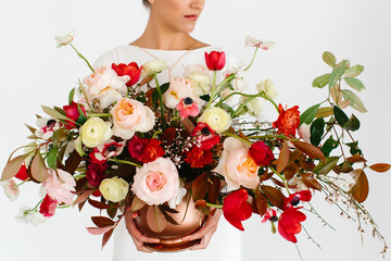 Closeup photograph of a woman showing a bunch of assorted flowers.