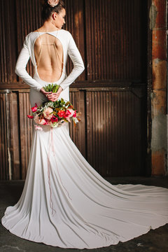 A beautiful woman in a all white dress backless dress