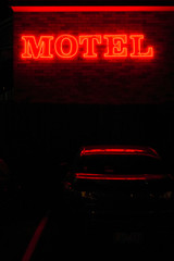 Motel sign at night with car parked underneath
