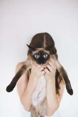 Young woman holding siamese cat