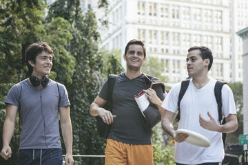 Men Friends Hanging Out Together Walking Through Urban Park in Downtown New York's Financial District