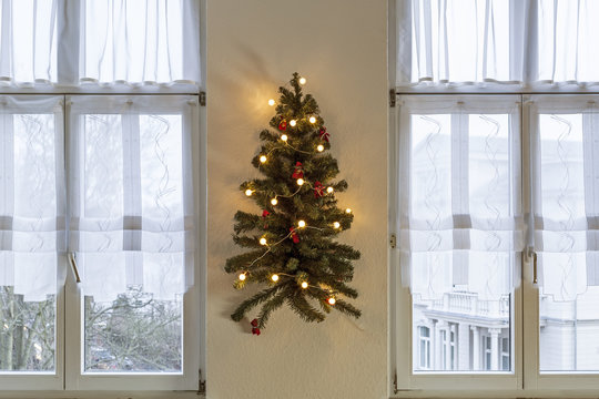Decorated artificial Christmas tree hangs on a wall between two windows