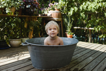 Little short-haired girl sits washing outside in an old-fashioned tin tub.