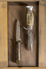 Two old hunting knives on a wooden board