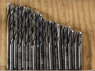Different drill bits on wooden background