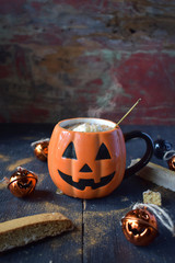 pumpkin spice coffee drink in pumpkin mug with steam