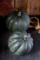 two whole acorn squash in rustic setting