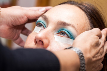 Make up artist using masking tape to create cat eyes
