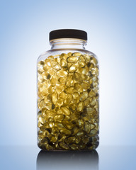 Amber glow through bottle full of fish oil omega 3 and vitamin D supplement gel capsules. on blue background