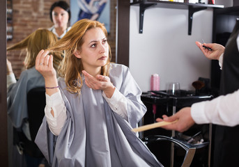 Unhappy woman in hairdress salon