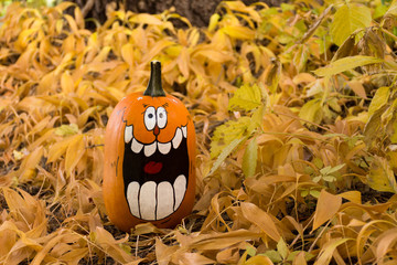 A laughing pumpkin with painted faces that have oval eyes and big teeth. The pumpkin is sitting in dried leaves with a tree trunk in the background.