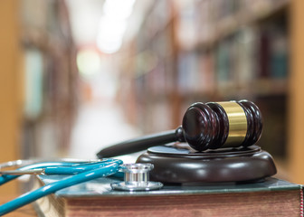 Forensic medicine investigation or malpractice justice concept with judge gavel and medical stethoscope on law textbook in library archive study room