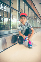 Happy asian child sitting and tying to tie shoelaces near walkway in modern airport.
