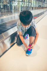 Asian child sitting and tying to tie shoelaces near walkway in modern airport.