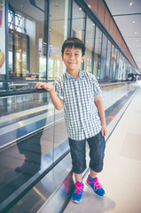 Happy asian child standing and smiling near electric speedwalk in modern airport.